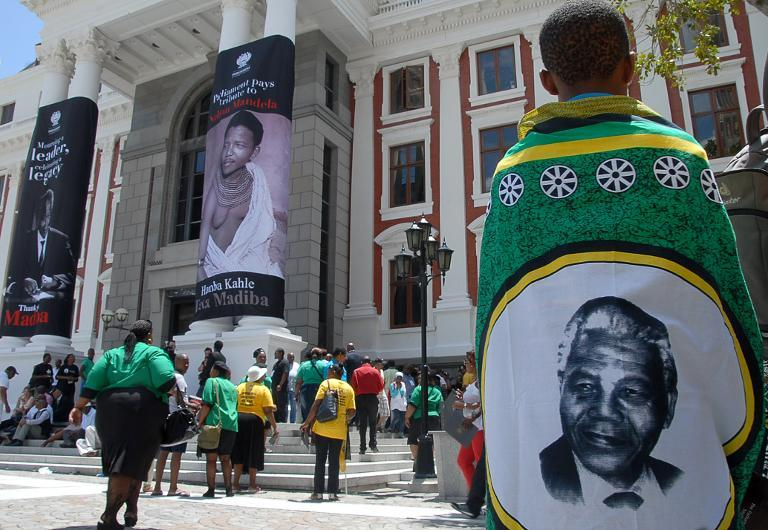 A man wearing a traditional garment with Nelson Mandela's portrait outside parliament in Cape Town (Masixole Feni-AFP)