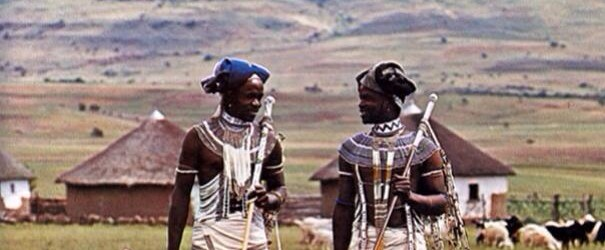 Xhosa men in tradional clothing talking in a village, mountains behind
